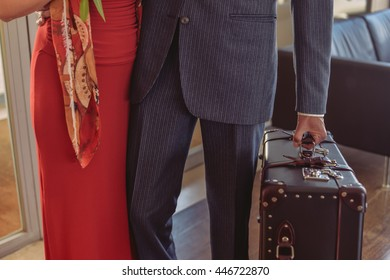 Closeup on hand of elegant people walking at reception holding suitcase. Beautiful hugging couple