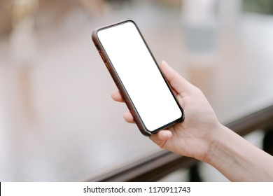 close-up on hand holding phone showing white screen on desk at coffee shop.