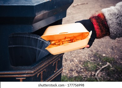 Closeup on a hand putting a box of chips in the bin