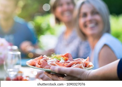 Close-up on a hand serving a dish of dry ham and cheese to friends gathered around a table in a garden to have fun together.