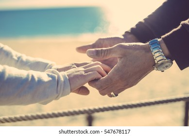 Closeup on hands. Back view silhouette of male and female couple on holiday travel vacation sunshine beach. Blue sunny ocean sky background. Lovely valentines day