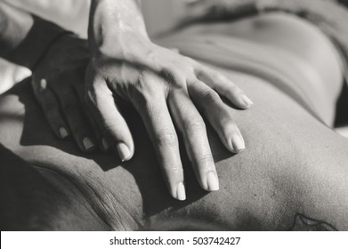Closeup on hands doing back massage at spa, sunny window background