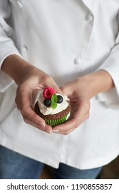 Close-up on hands of female pastry chef in white gown with muffin or a cupcake decorated with wild berries
