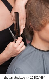 closeup on hands of hairdresser cutting hair of man client. closeup on man head sitting in hair salon