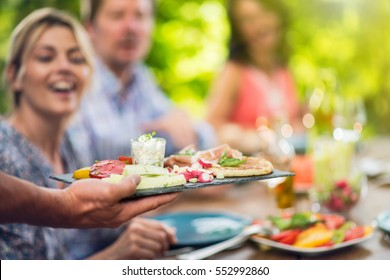 Close-up on hands holding a tray with a preparation of vegetables and parma ham. In the background, friends gathered around the table on the terrace