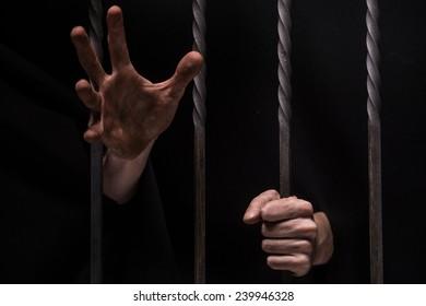 closeup on hands of man sitting in jail. Man behind jail bars on black background reaching