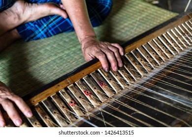 Close-up on the hands of an old woman weaving sedge mat in the small village of Ben Tre in the Mekong delta region, Vietnam