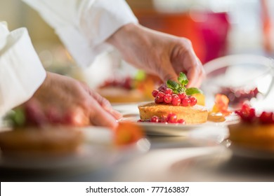 Close-up on the hands of the pastry chef decorating a cake with redcurrants and a mint leaf before serving.