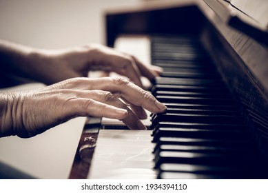 Closeup on hands playing piano at home in a calm atmosphere