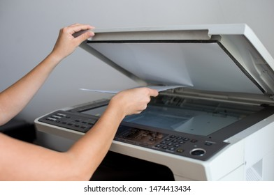 Close-up on the hands of a woman doing photocopies in the office. Woman making photocopy using copier in office. Female secretary making photocopies on machine in office.