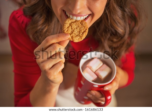 Closeup on happy young housewife drinking hot chocolate and eating christmas cookie