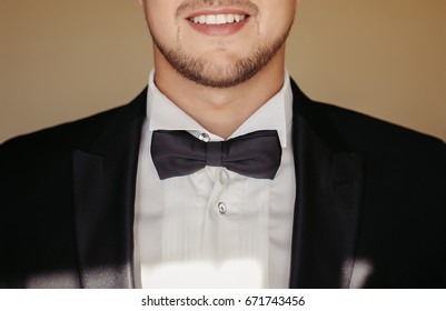 Closeup on a happy young man tying a bow tie.