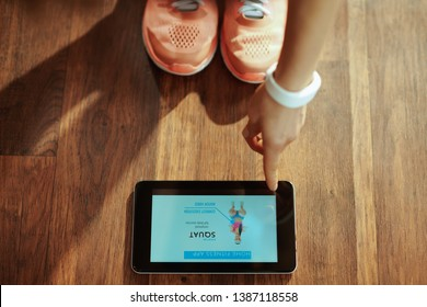 Closeup on healthy sports woman in fitness clothes in the modern living room using home workout trainer app in tablet PC.