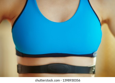 Closeup on healthy woman in sport clothes in the modern living room wearing heart rate monitor.
