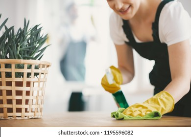 Close-up on housewife with yellow gloves and cloth cleaning a table at home