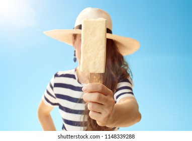 Closeup on ice cream on a stick in a hand of woman against blue sky