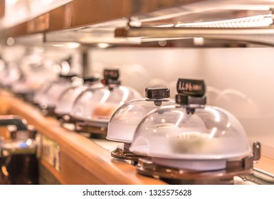 Close-up on Japanese Conveyor belt sushi restaurant where plates with sushi are placed on a rotating rail protected with a clear plastic lid.