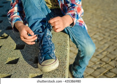 Closeup on kid hands tying laces ready for sport, school fun. Outside sunny background
