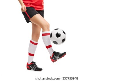 Close-up on the legs of a female football player jugling with a ball isolated on white background