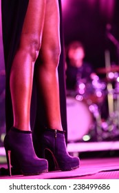 Closeup on legs of a female singer with stiletto heels on stage with a blurred drummer in the back.