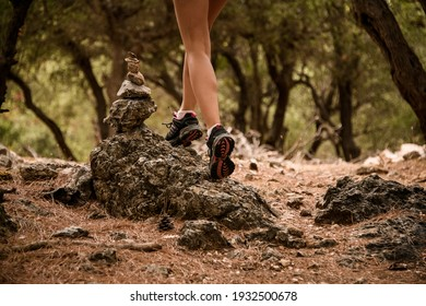 close-up on legs of woman walking on stones located along hiking trail in pine forest