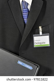 Closeup on male business suit with conference folder and delegate badge. The conference logo has been falsified