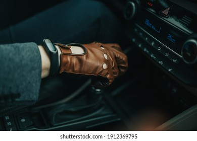 Close-up on male hand gripping gearstick of a manual car with brown leather driver gloves on and black smart watch on right hand