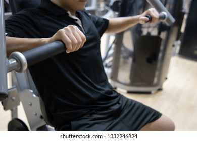 Close-up on a man doing vertical bench press machine in a gym