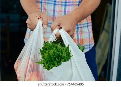 Closeup on man hand holding shopping bag with vegetables green grocery. Consumerism, variety merchandise background