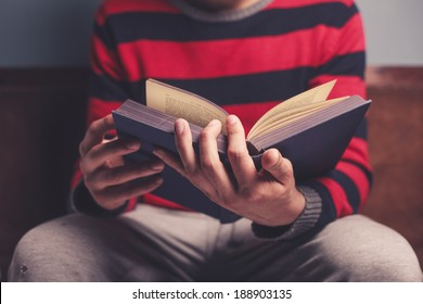 Closeup on a man reading a big heavy book