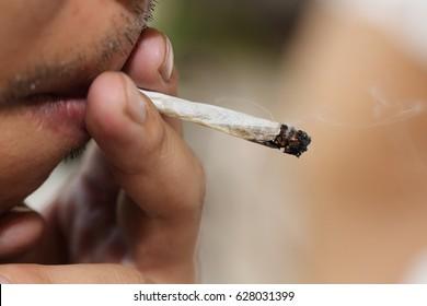 close-up on a man smoking marijuana cigarette in amsterdam