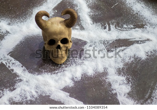 Close-up on man`s skull with horns on satan`s pentacle on floor