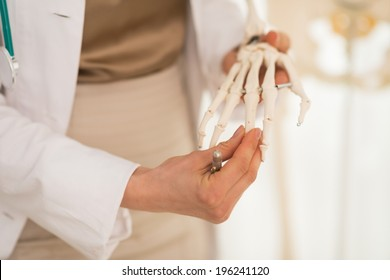 Closeup on medical doctor woman teaching anatomy using human skeleton model