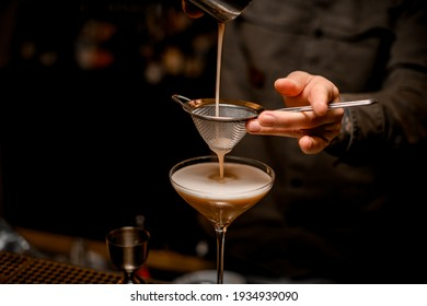 close-up on metal sieve through which male bartender pours frothy espresso martini cocktail into glass