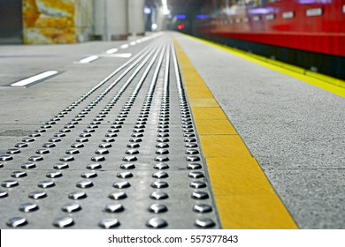 Close-up on metal tactile strips with an yellow line - for visually impaired (handicapped) and people with blindness - on a platform edge of an underground station - Warsaw Metro, Poland