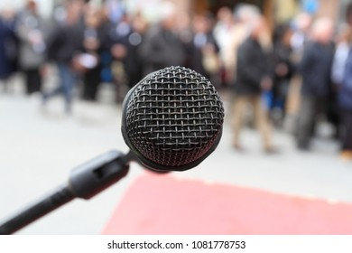 close-up on the microphone and the crowd blurred behind