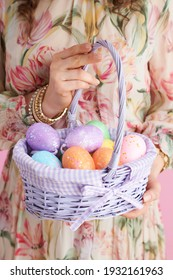 Closeup on middle aged woman with basket of easter eggs against pink background.