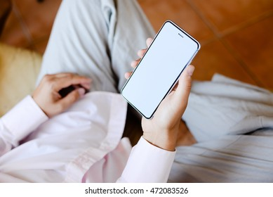 Closeup on mobile phone in hand of man sitting on couch. Top side view mock up background
