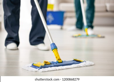 Close-up on mop on the floor holding by cleaning expert while purifying interior