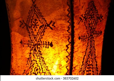 Close-up on Moroccan lamp on black background. Handmade traditional henna lamp from Morocco. Tattooed henna designs and symbols on lit leather lamp. Yellow orange cast.