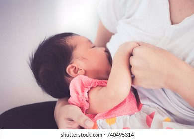 Closeup on mother hand holding baby hand while mother breastfeeding her newborn baby girl. Baby happy while drinking milk from mother's breast. Vintage color tone.