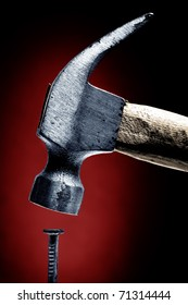 closeup on nail and hammer, red background