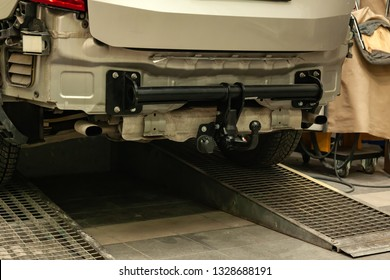 Close-up on a new black tow hitch installed on a modern car with a beige-colored bumper removed in a vehicle repair shop. The device for the transport of the trailer in the workshop.