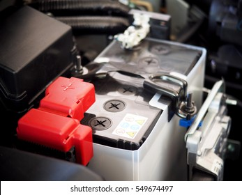 close-up on new small eco car battery installed in the compartment showing good arrangement and safety, clear communicated design of electrical connector and warning pictogram signs on the top cover