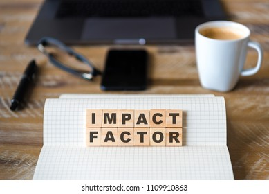 Closeup on notebook over vintage desk surface, front focus on wooden blocks with letters making Impact Factor text. Business concept image with office tools and coffee cup in background