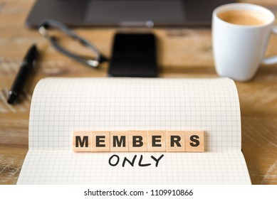 Closeup on notebook over vintage desk surface, front focus on wooden blocks with letters making Members Only text. Business concept image with office tools and coffee cup in background