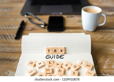 Closeup on notebook over vintage desk surface, front focus on wooden blocks with letters making Tax Guide text. Business concept image with office tools and coffee cup in background