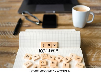 Closeup on notebook over vintage desk surface, front focus on wooden blocks with letters making Tax Relief text. Business concept image with office tools and coffee cup in background