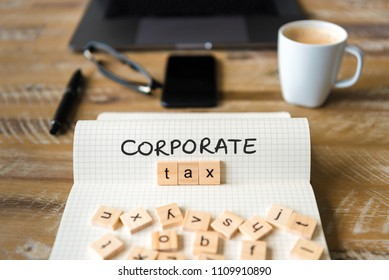 Closeup on notebook over vintage desk surface, front focus on wooden blocks with letters making Corporate Tax text. Business concept image with office tools and coffee cup in background