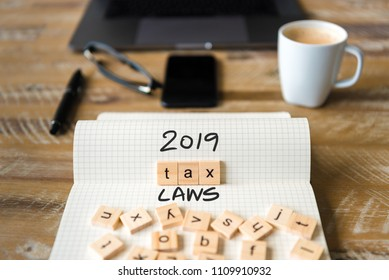Closeup on notebook over vintage desk surface, front focus on wooden blocks with letters making 2019 Tax Laws text. Business concept image with office tools and coffee cup in background